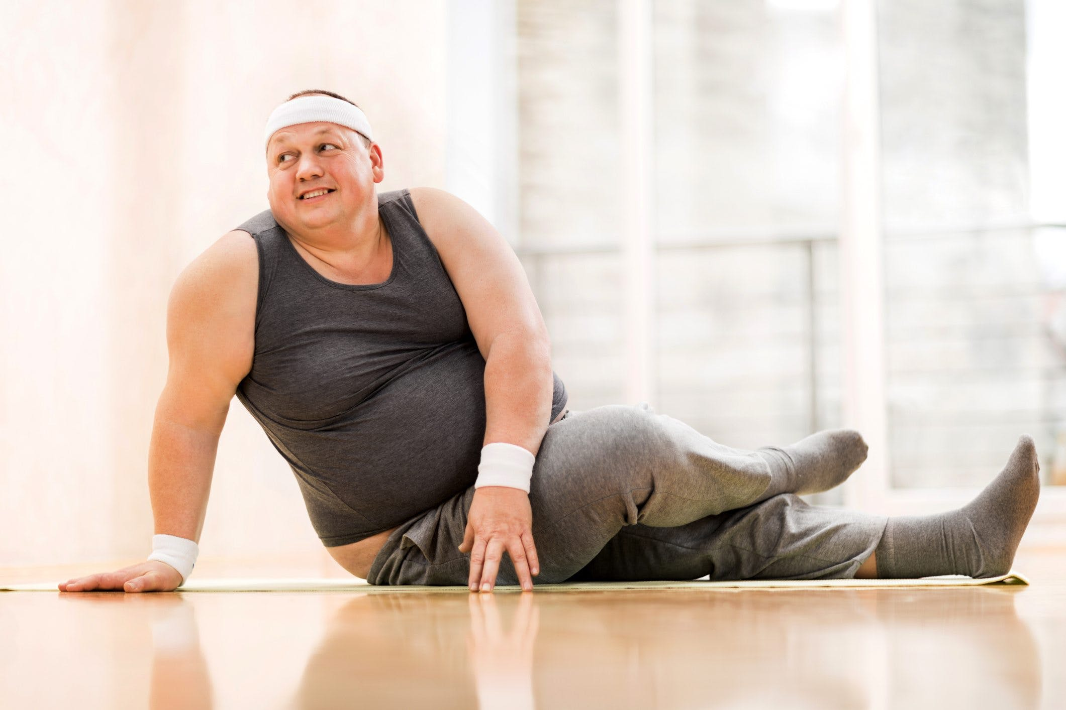 Smiling fat man stretching on the floor.