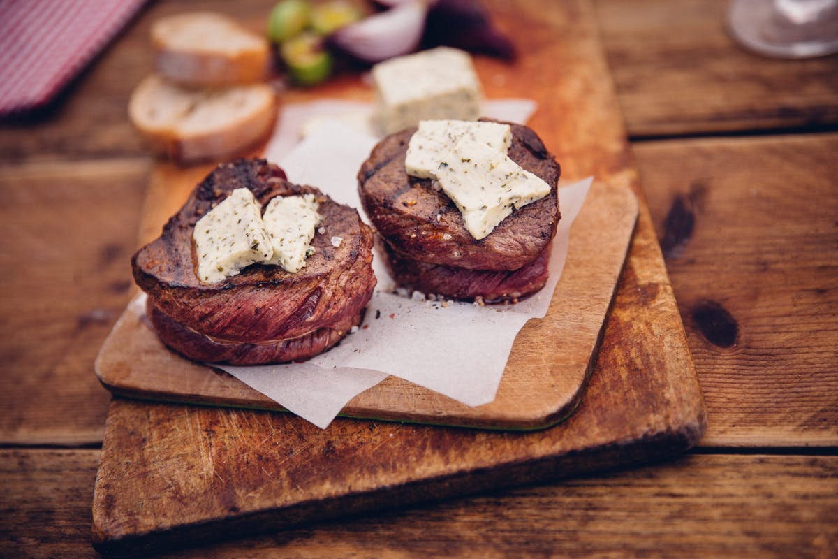 Tender steak medallions topped with cheese on wooden boards