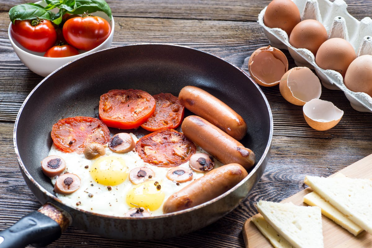 Fried breakfast with egg, sausages and baked tomato