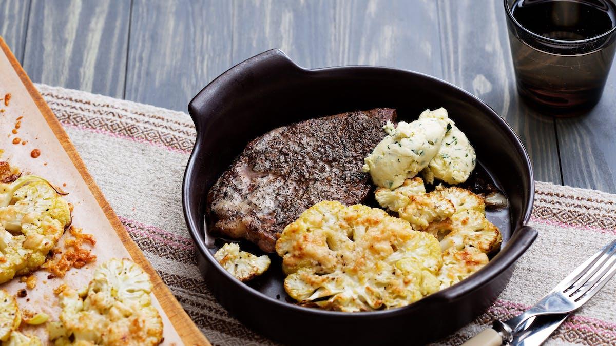 Chuletas de cerdo con coliflor asada al parmesano y mantequilla de hierbas