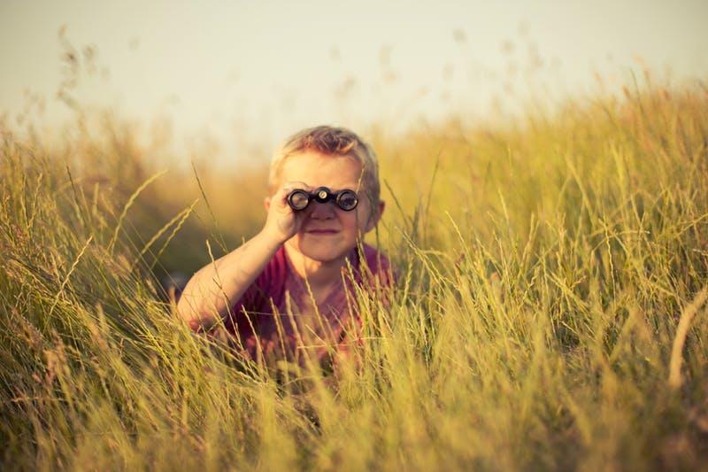 niño mirando con prismáticos