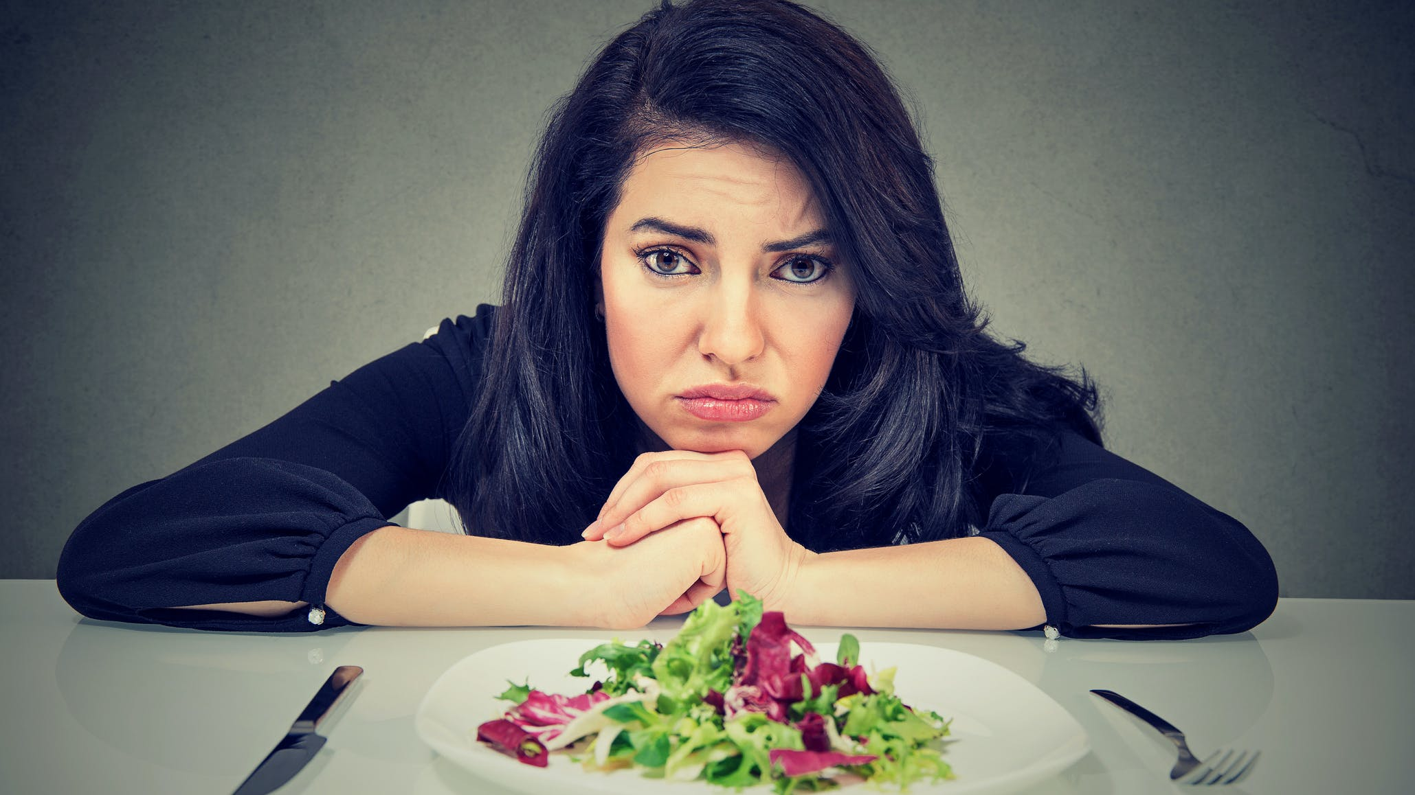 Mujer disgustada frente a plato