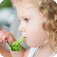 Niña comiendo brócoli
