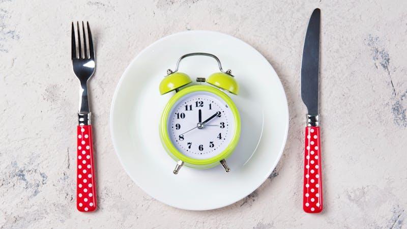 Reloj despertador sobre un plato con cubiertos