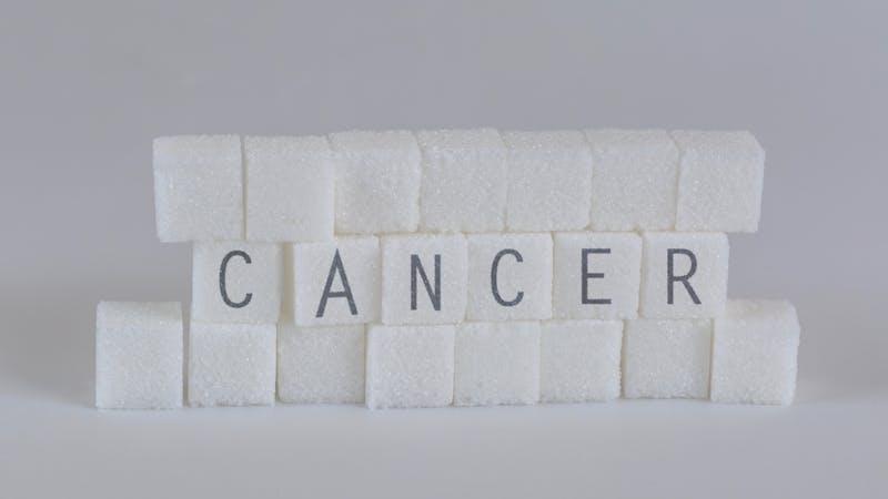 Terrones de azúcar con la palabra cáncer
