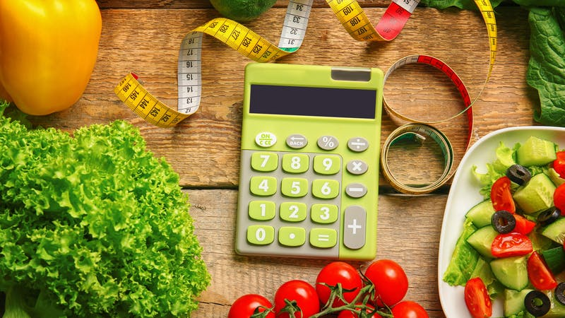 Calculator, measuring tape and set of healthy food on wooden table