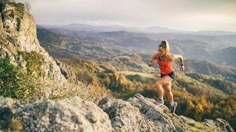 Mujer joven corriendo en sendero de montaña