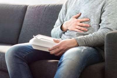 Hombre con mano sobre el estómago
