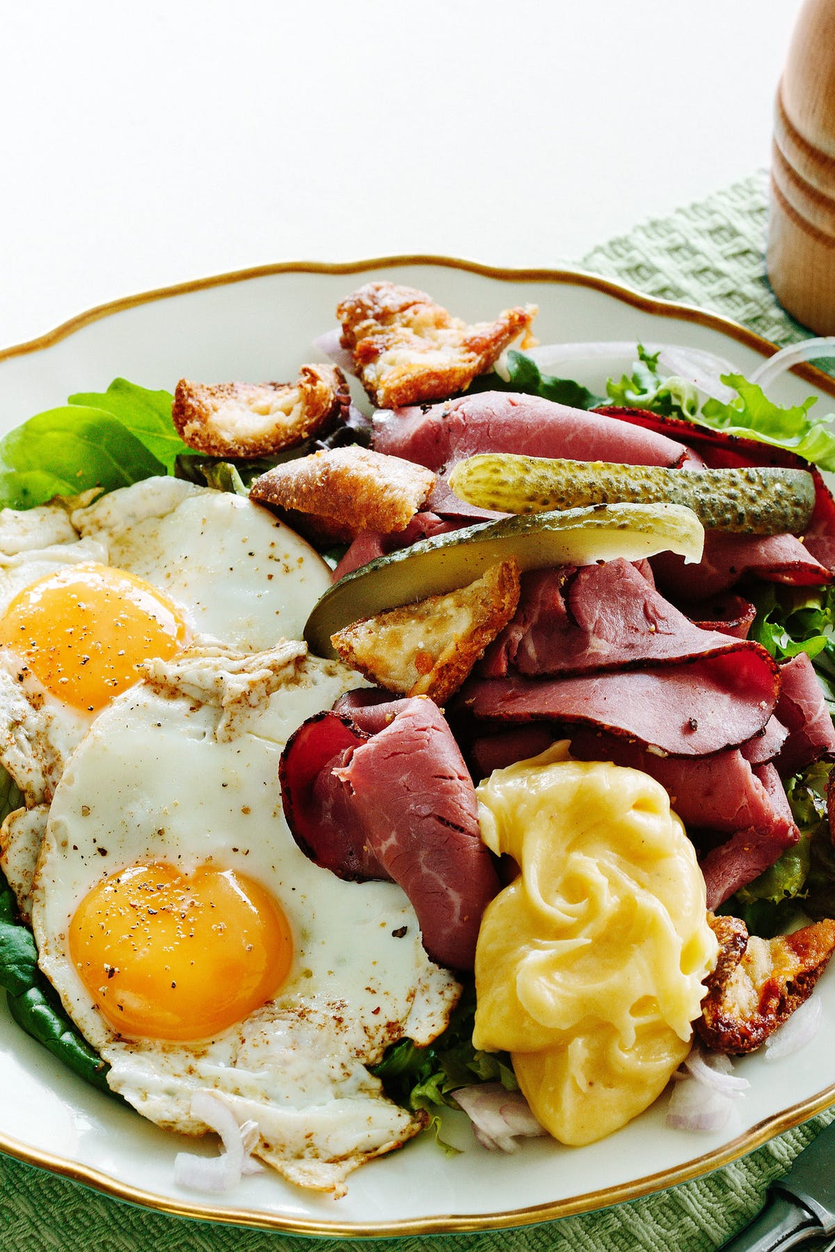 Ensalada keto de pastrami con huevos fritos y picatostes