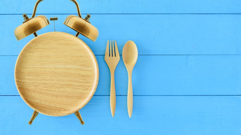 Intermittent fasting, diet and weight loss concept : Clock shaped wood dish, spoon and fork. Eco-friendly plate / kitchen utensil as alarm clock with ringing bell, depict alert or reminder time to eat