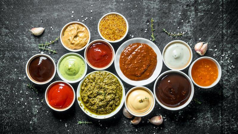 Pesto sauce, guacomole, ketchup, mustard, barbecue sauce in bowls.