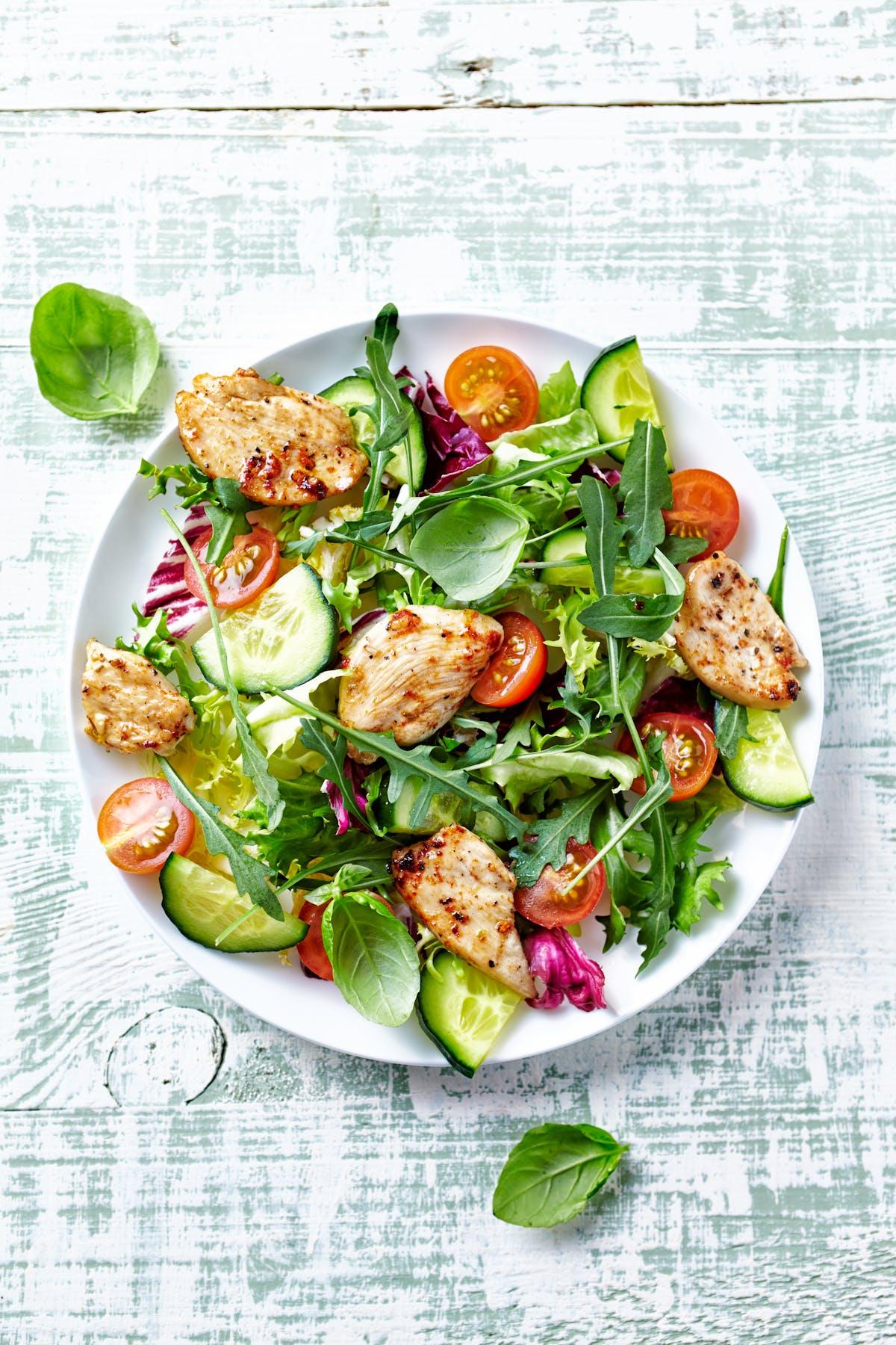 Ensalada de pollo con hojas verdes y tomate
