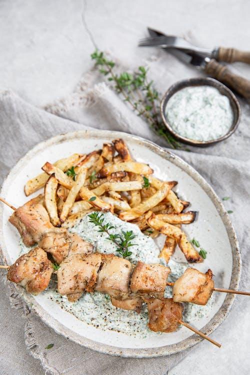 Brochetas de pollo con chips de apio y salsa de espinacas