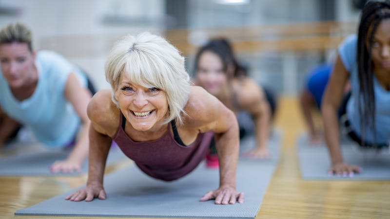 Senior Woman in Fitness Class in a Plank Pose Smiling stock photo