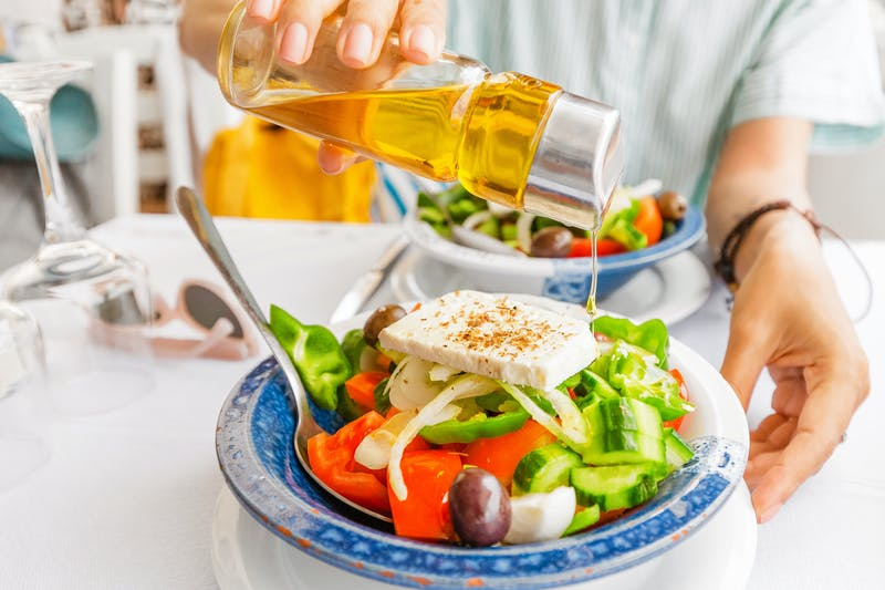 Woman pouring delicious Olive oil into greek salad in restaurant. Healthy food and vegetarian concept