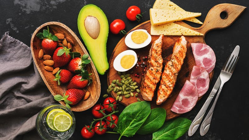 Grilled salmon with boiled egg, ham, vegetables and strawberries on a dark background. Keto diet dinner or lunch. Top view, flat lay.