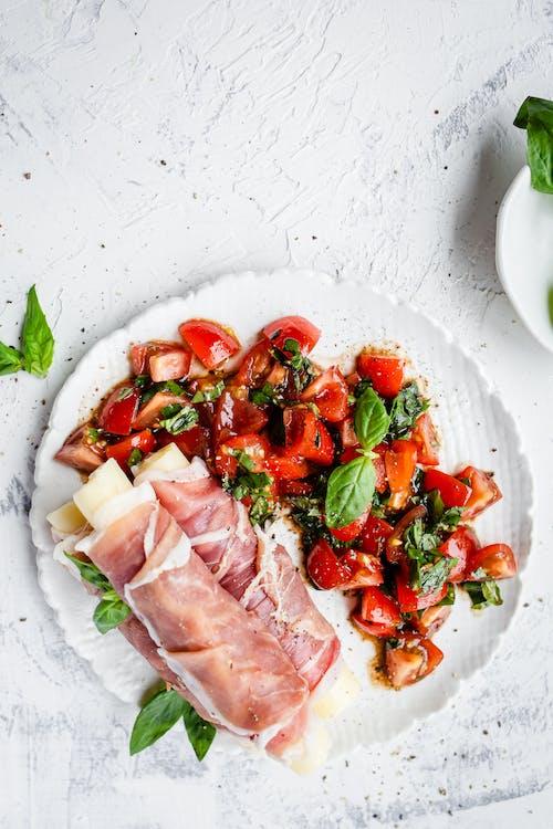 Palitos de mozzarella envueltos en prosciutto con ensalada de tomate y albahaca