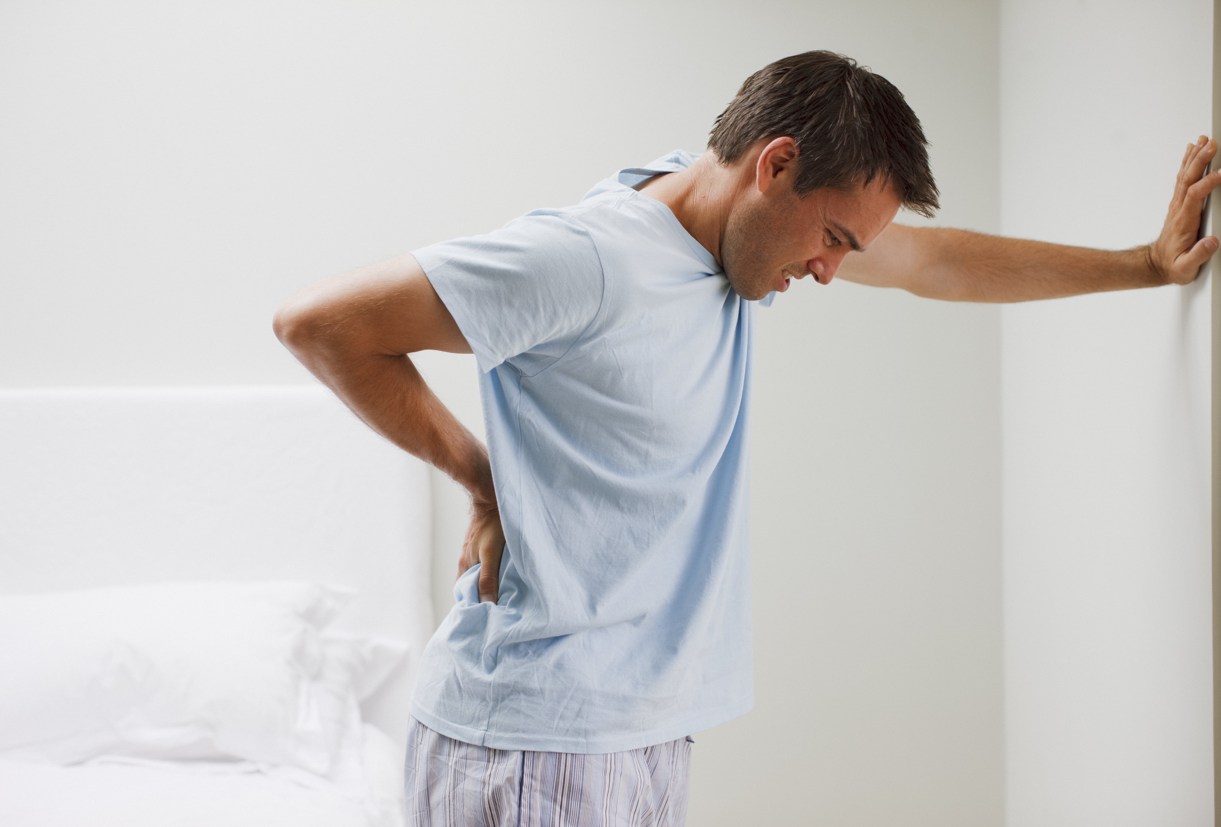 Man with backache leaning against wall