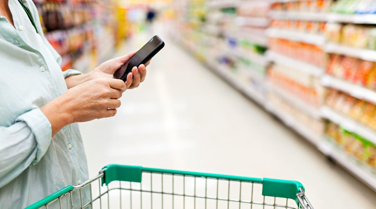 在超市里用智能手机的女人