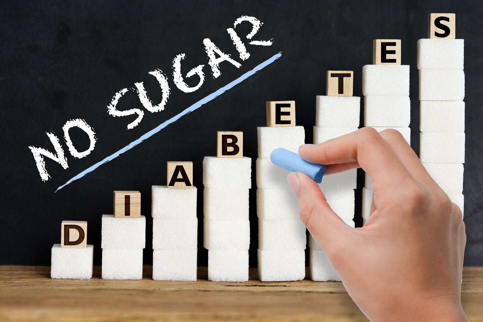 No sugar advice handwritten on blackboard above sugar cubes scale, suggesting diabetes risk