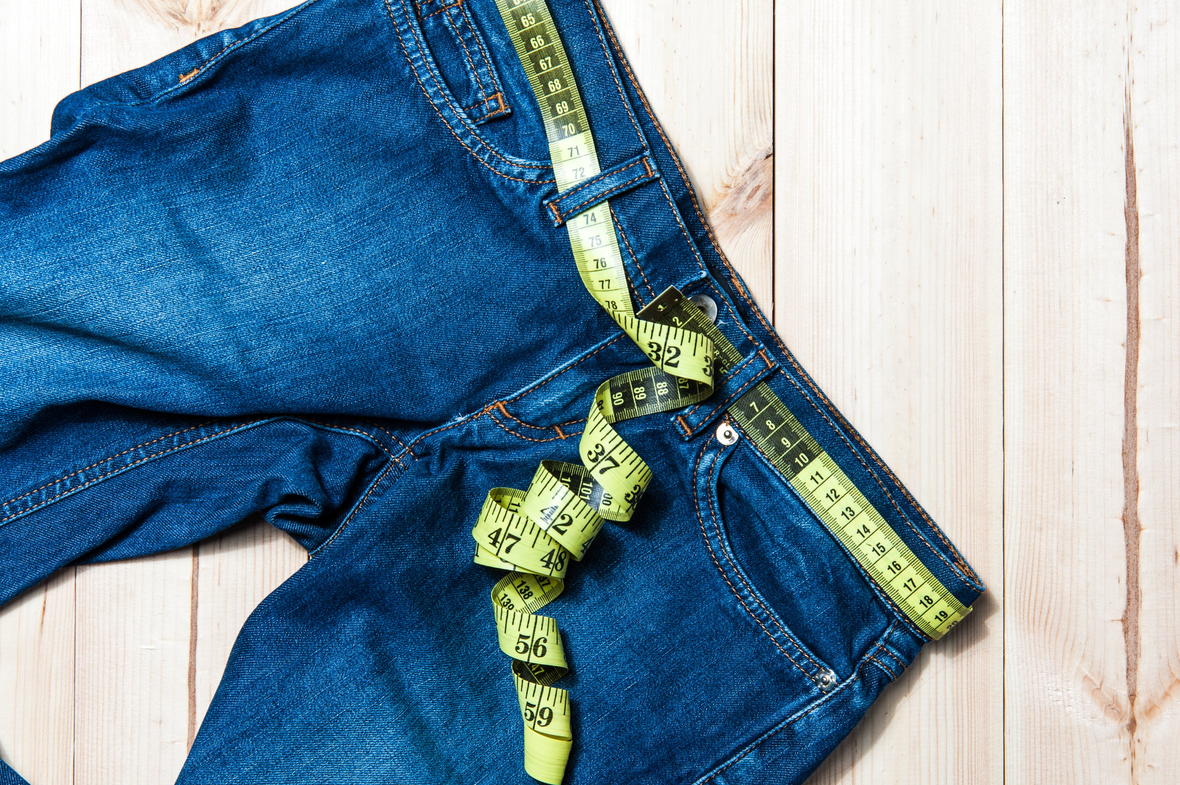 jeans and centimeter on a wooden background