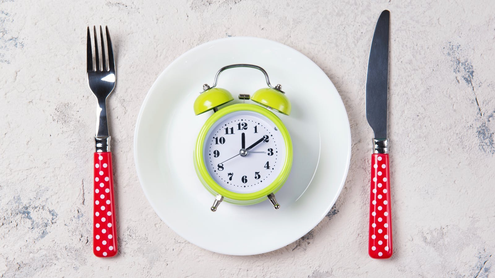Alarm clock with bells on the plate with fork and knife, lunch time concept, top view with copy space