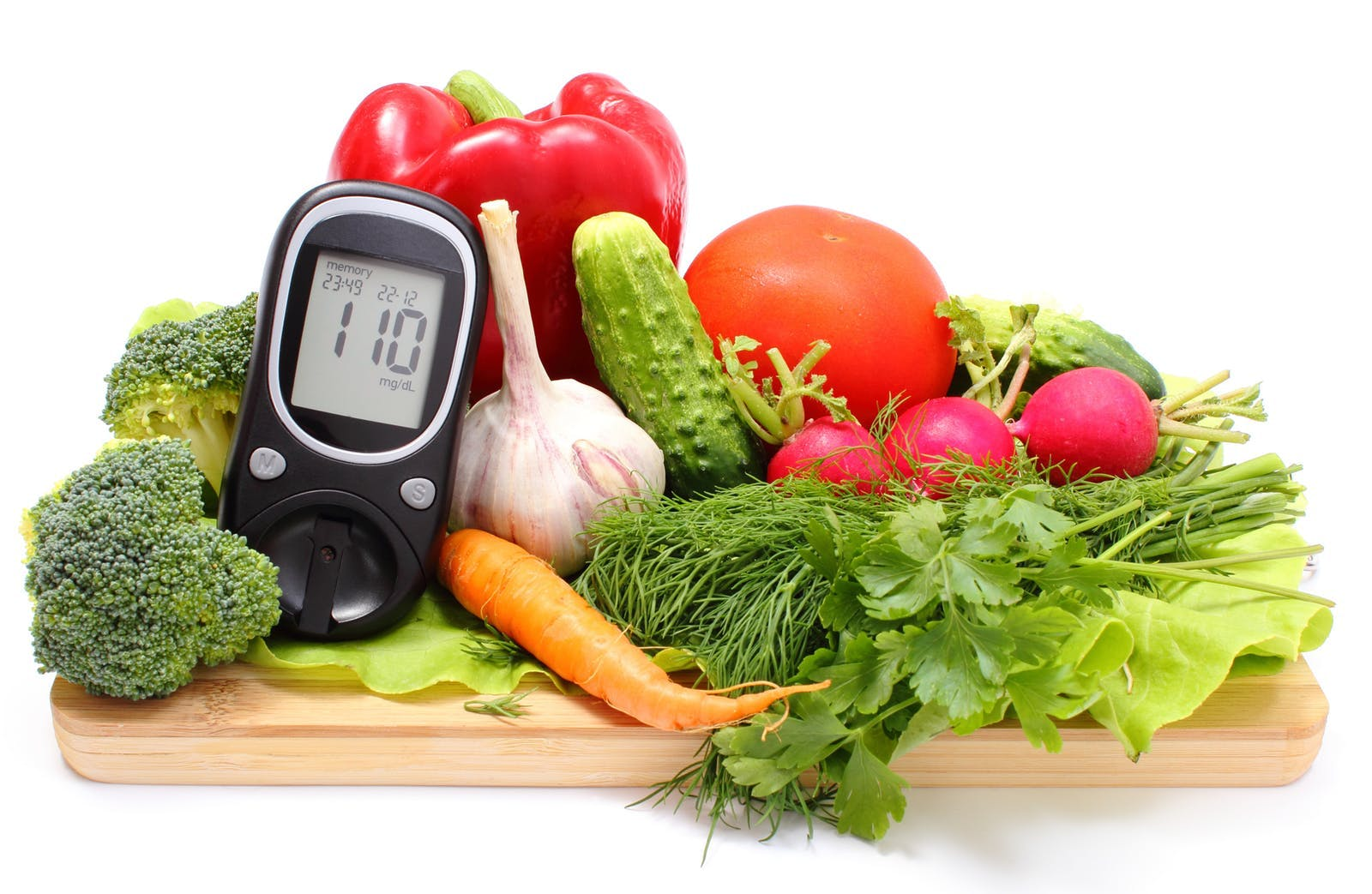 Glucometer and fresh vegetables on wooden cutting board