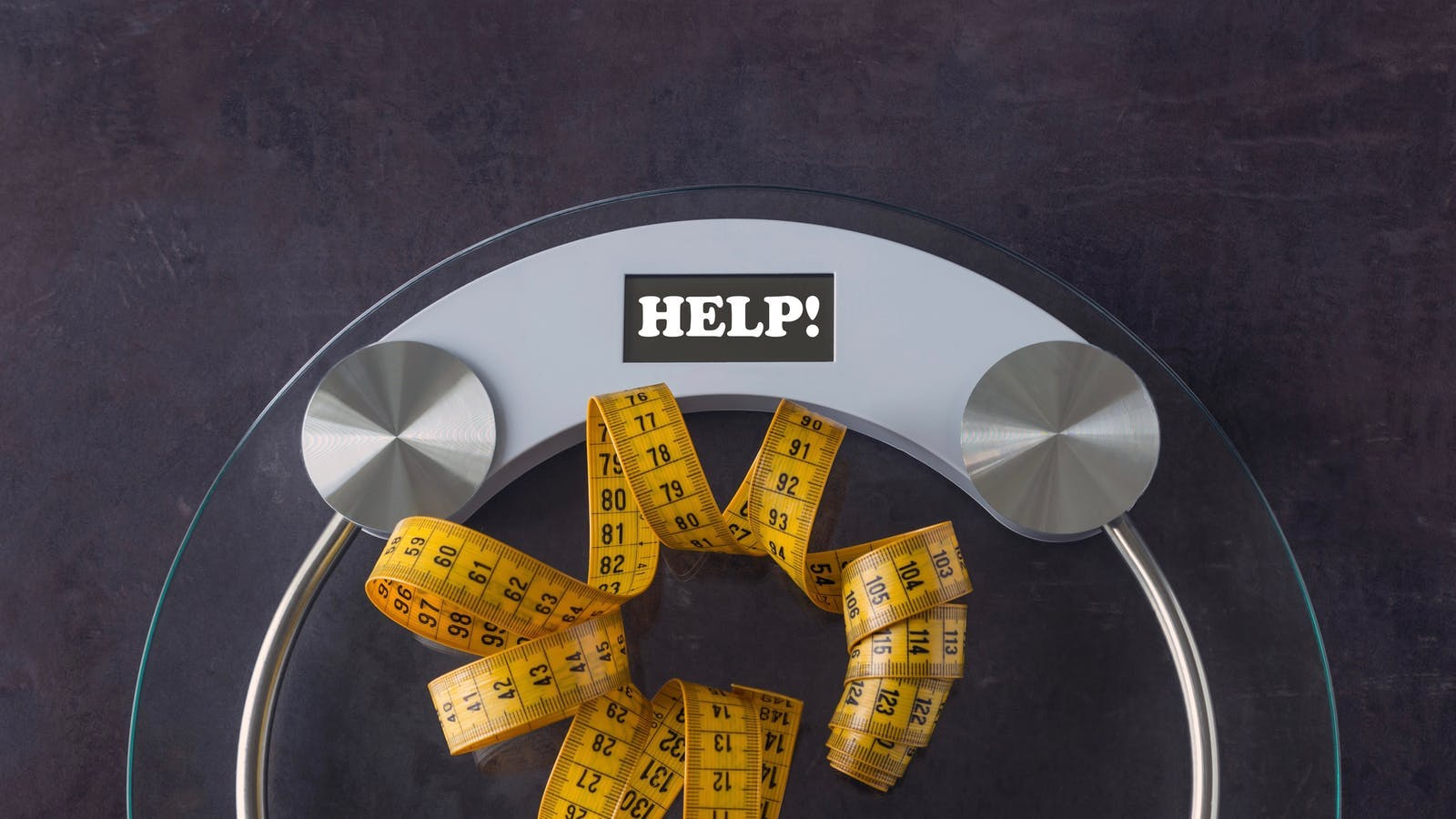 Weight scale with a measuring tape. Concept- lifestyle, sports and diet for weight loss. Copy space. On the measuring scale written word - HELP!