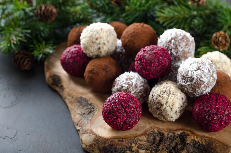 Homemade vegan chocolate candies with dried raspberry, grated coconut, nuts, cocoa on a wooden board made of olive tree and dark stone background. Fir branches on the back. Selective focus, copyspace