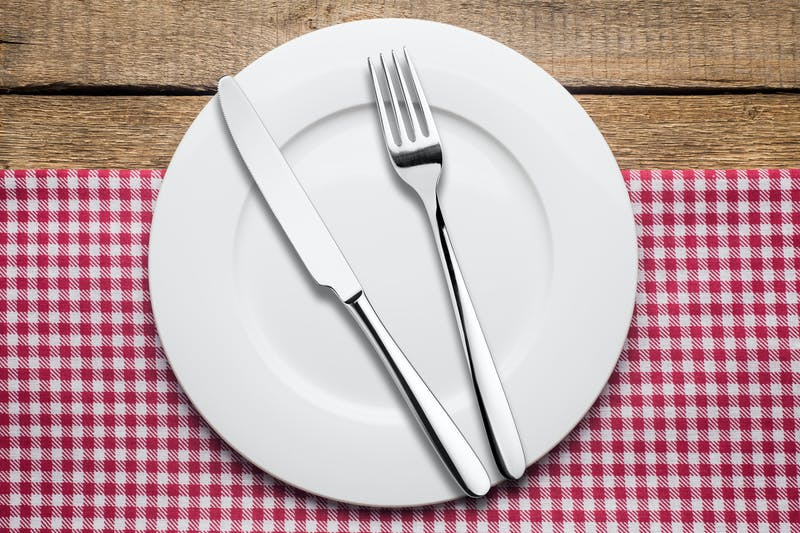 empty plate on a wooden background, a napkin in a red and white