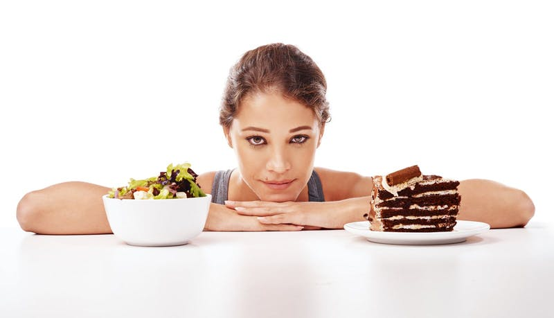 Woman-choosing-between-salad-or-chocolate-cake