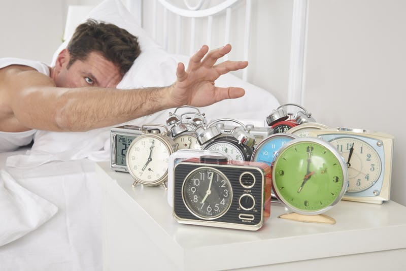 Man shutting off alarm clocks