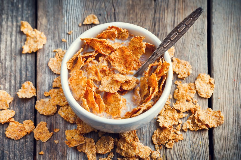 Breakfast cereal wheat flakes in bowl with milk