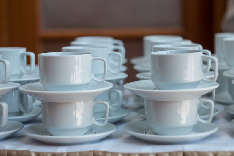 White cups for tea piled on table with plates for coffee-break. Catering concept.
