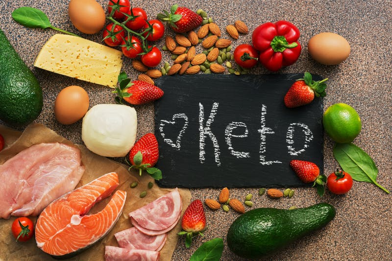 Keto diet food. Healthy low carbs products.Keto diet concept. Vegetables, fish, meat, nuts, seeds, strawberries, cheese. Top view. Signboard.