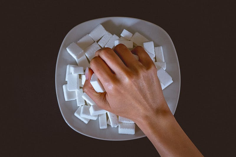 Female hand grabbing a bunch of sugar cubes from the plate on the table