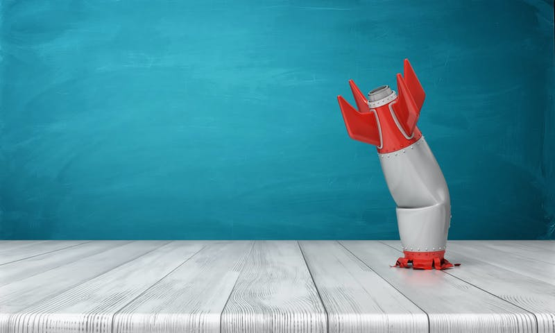 3d rendering of a red and silver realistic model of a retro rocket stands crashed into a wooden desk on a blue background.