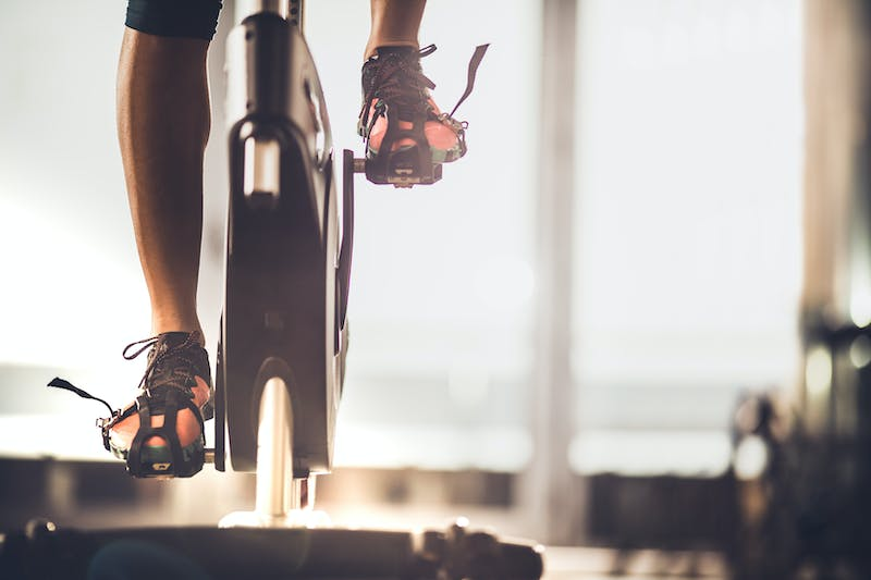 Unrecognizable female athlete exercising on exercise bike in a gym.