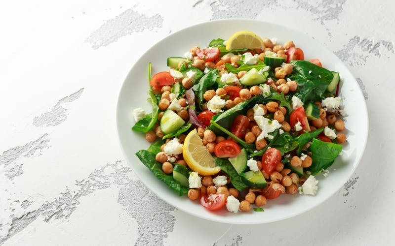 Chickpeas Salad with cucumber, tomatoes, feta cheese and green mix in a white plate. healthy food.