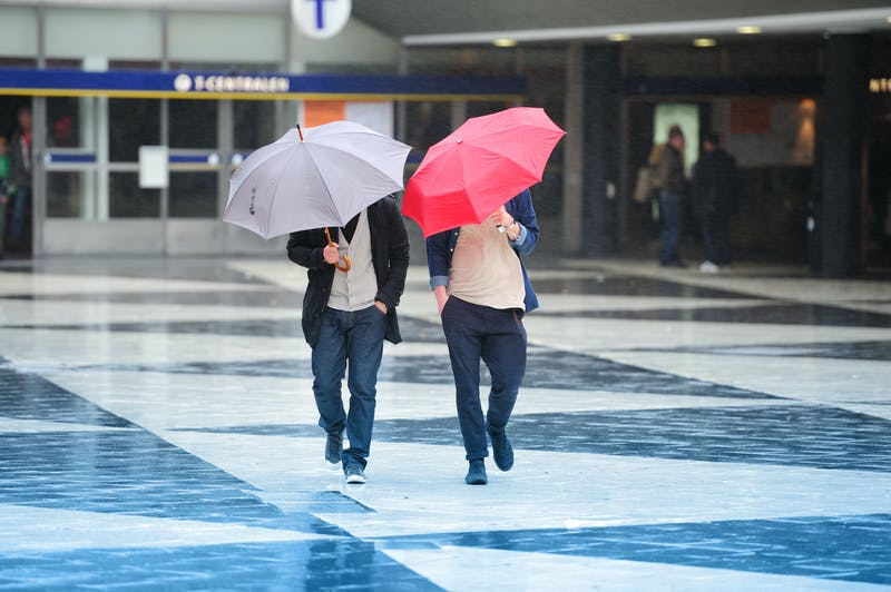 Pedestrians and umbrella in hard wind