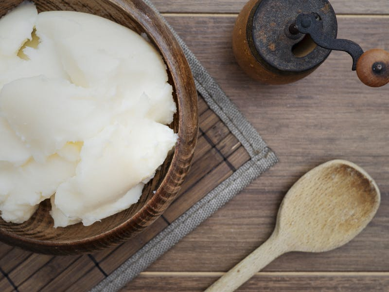 Pork fat (lard) in wooden bowl on rustic background