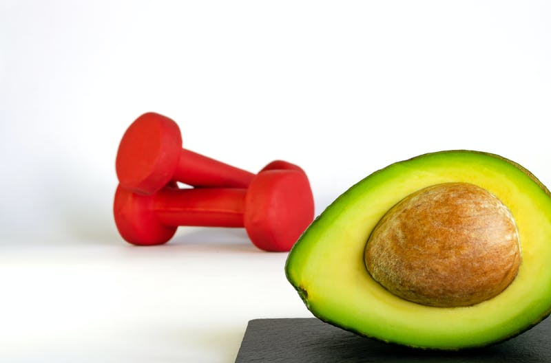 Fresh avocado with unfocused red dumbbells on background. Concept of healthy eating and sports.