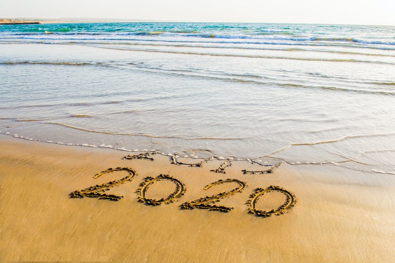 Happy New Year 2020 text on the sea beach. Abstract background photo of coming New Year 2020 and leaving year of 2019