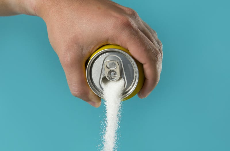 man hand holding lemon refresh drink can pouring sugar stream in sweet and calories content of soda and energy drinks