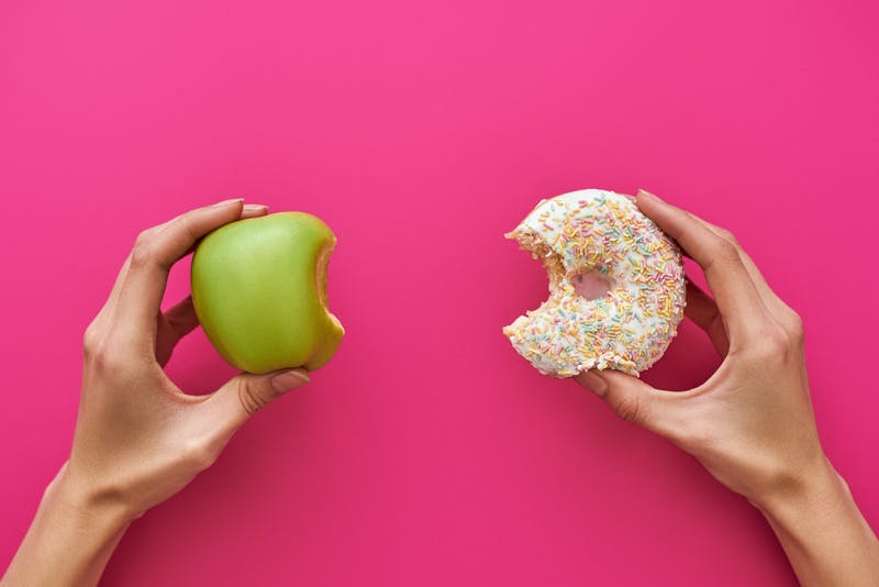 Dieting or good health concept. Young woman trying to choose between apple and donut