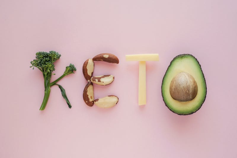 Keto word made from Ketogenic diet, low carb, healthy food on pink pastel background
