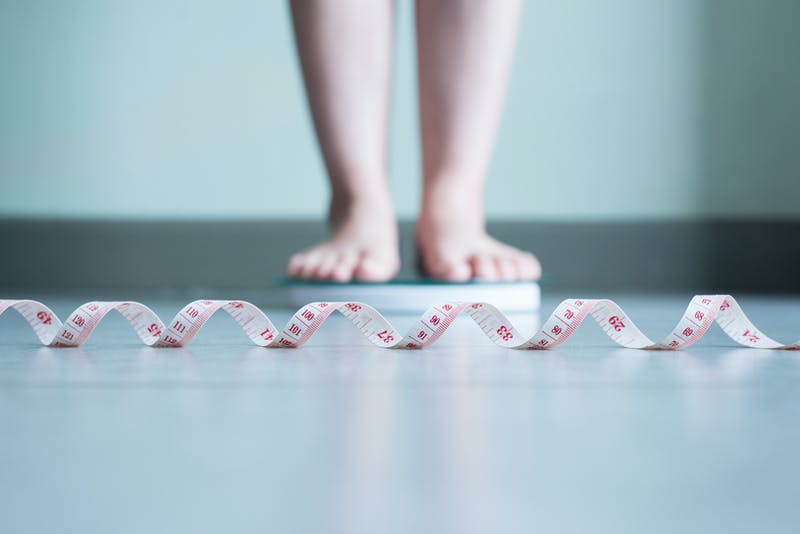 Blured of woman foot standing on weigh scales with tape measure in foreground
