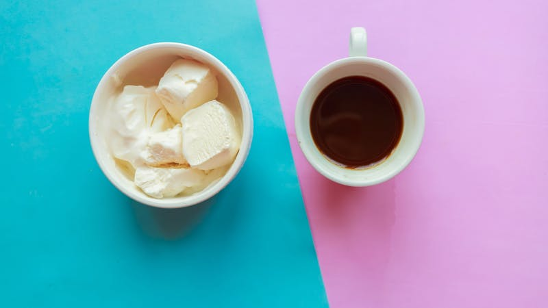 Vanilla ice cream bowl and coffee cup on pink and blue background, top view