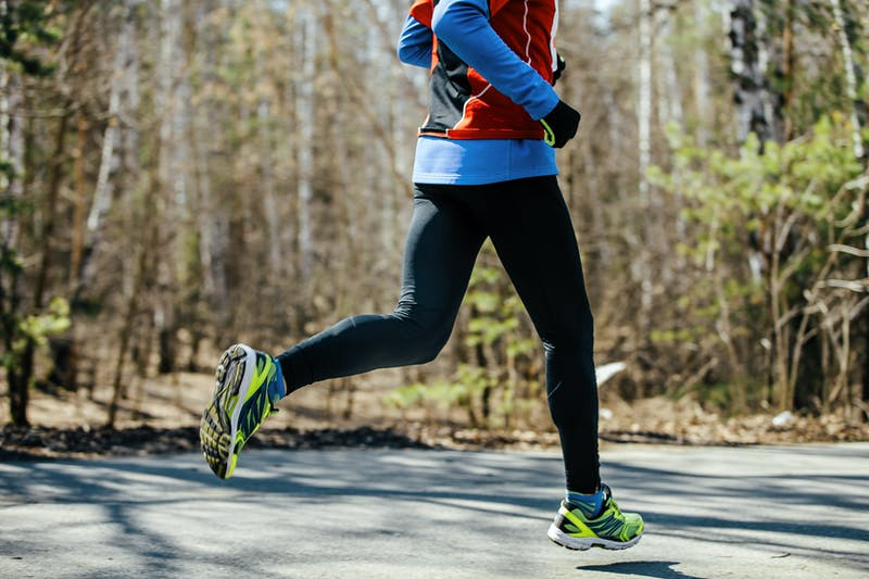 feet athletic male runner runs asphalt road in spring park