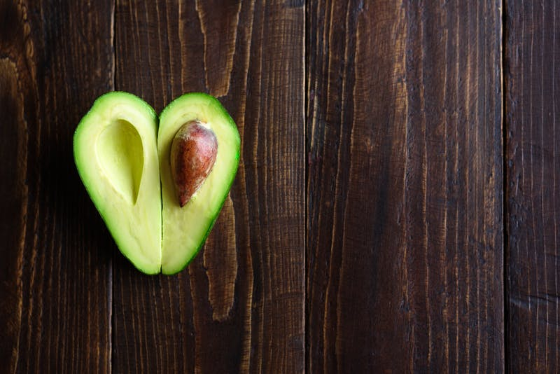 Heart shaped avocado on wooden background